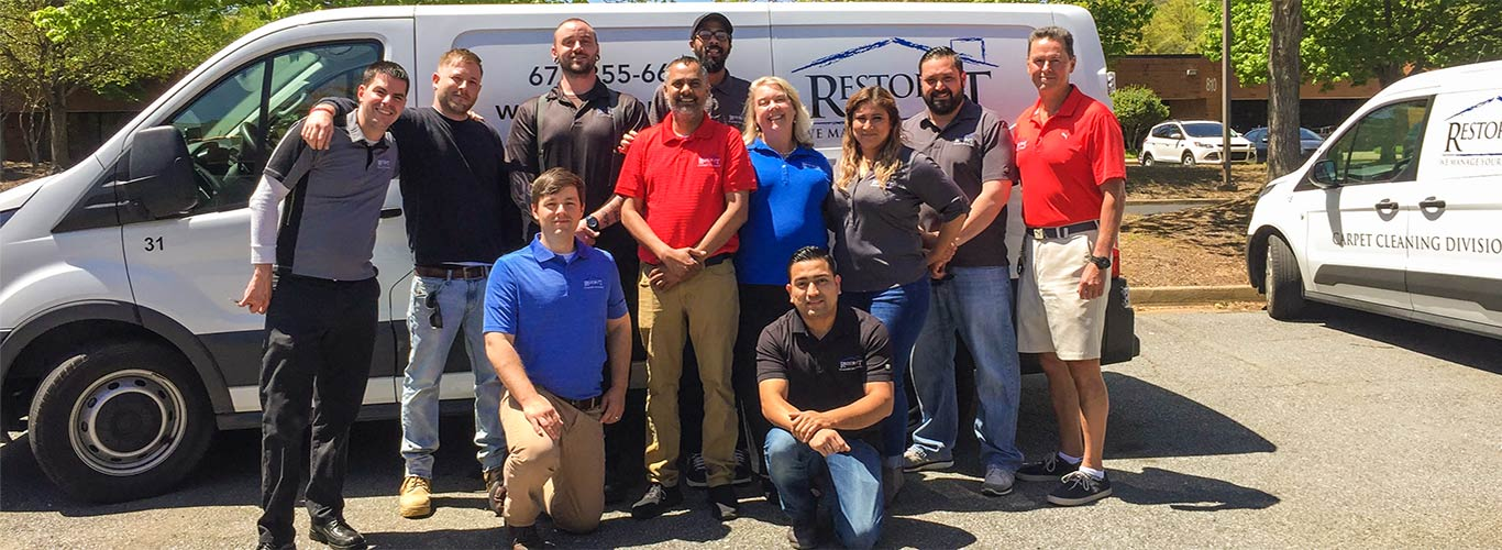 The Restor-It team posing in front of their service sprinter vans